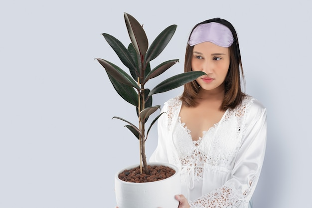 Asian woman in a white satin nightgown wearing lace robe holding rubber plant in white pot. a lady holding an air purifying plants in her hand against a gray background and space left side.