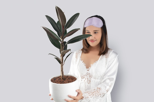 Asian woman in a white satin nightgown wearing lace robe holding rubber plant in white pot.