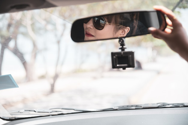 Asian woman in white shirt is looking into the mirror and smiling while sitting in her car