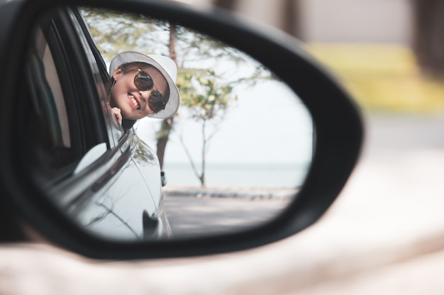 Asian woman in white shirt is looking into the side view mirror and smiling while sitting in her car, travel concept.