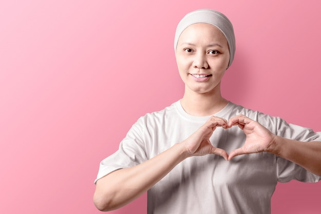 Asian woman in a white shirt showing a heart sign with her hands on pink