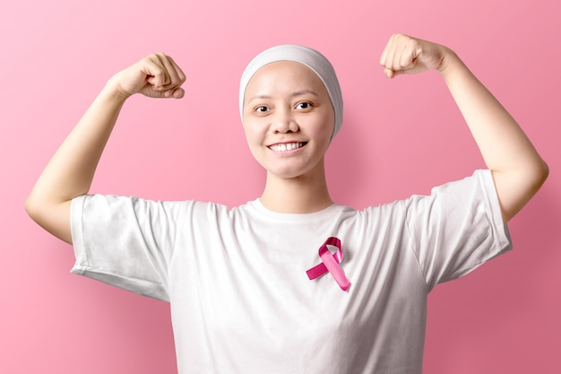 Asian woman in a white shirt with pink ribbon over pink