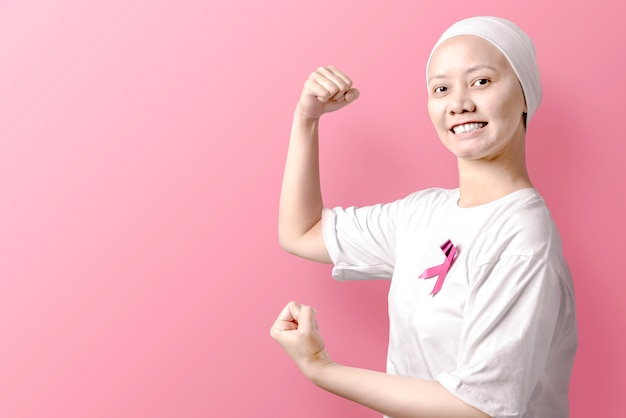 Asian woman in a white shirt with a pink ribbon over pink