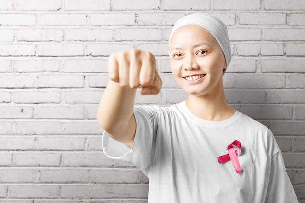 Asian woman in a white shirt with a pink ribbon over a white wall