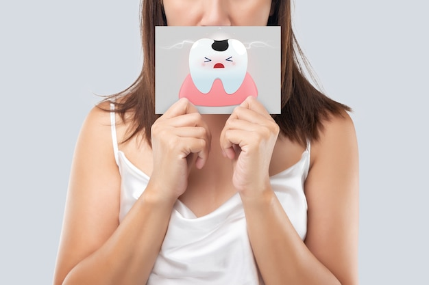 Asian woman in the white wear holding a white paper the caries cartoon picture of his mouth against the gray background, decayed tooth, the concept with healthcare gums and teeth