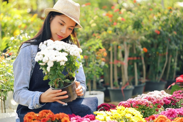 An asian woman who owns a flower garden business is counting the flowers to match the customer order.