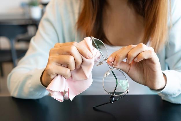 Азиатская женщина вытирает очки тканью. очки для чистки. крупным планом