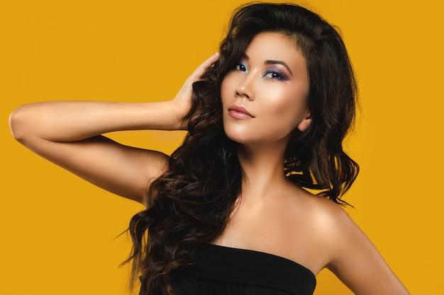 美しい巻き毛と黄色のメイクでアジアの女性