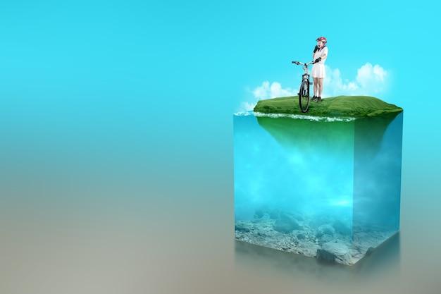 호수에 푸른 물의 수중 보기와 함께 필드에 그녀의 자전거 옆에 서 있는 자전거 헬멧을 쓴 아시아 여자. 환경 개념