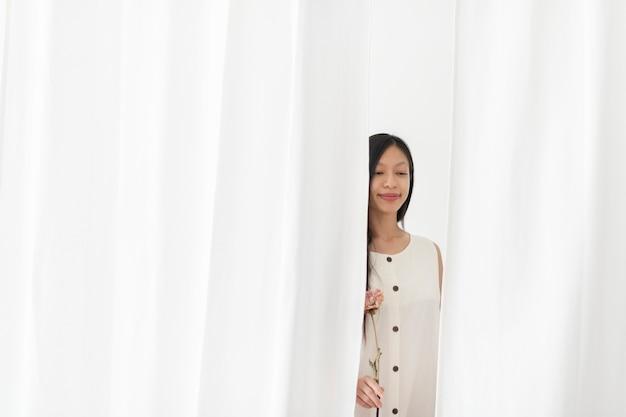흰색 커튼을 통해 걷는 손에 마른 분홍색 모란 꽃과 아시아 여자