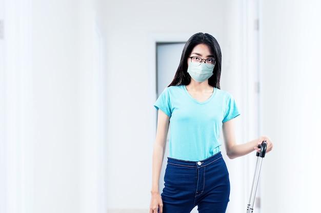 Азиатская женщина с маской для лица и очками, стоя с чемоданом в больнице. медицинский осмотр перед поездкой
