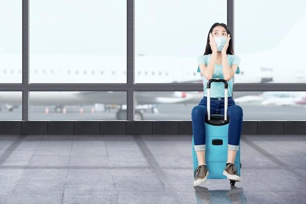 Азиатская женщина с маской для лица с чемоданом в аэропорту. путешествие в новой норме