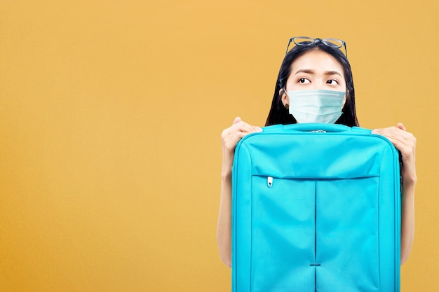 Азиатская женщина с маской для лица с чемоданом. путешествие в новой норме