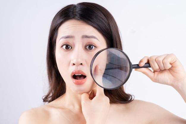 여드름이 나타날 때 놀란 표정으로 아시아 여자