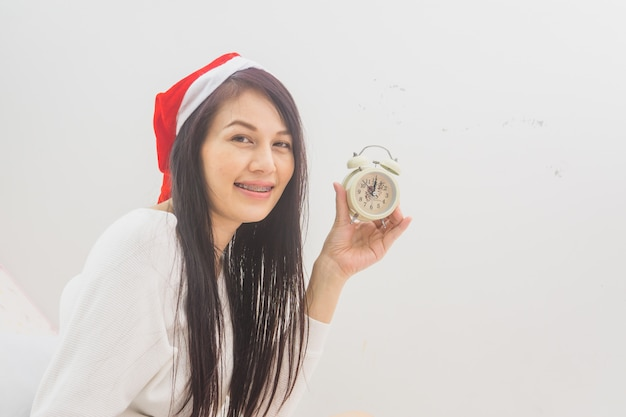 Asian woman with alarm clock waiting for christmas holiday.
