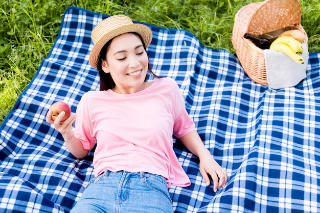 Asian woman with apple lying on plaid
