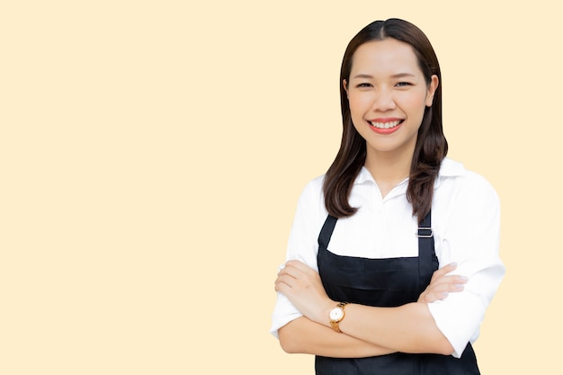 Asian woman with apron standing isolated on cream color background