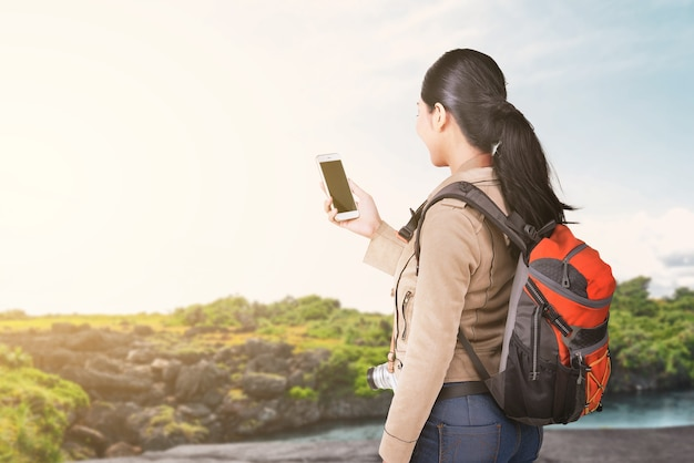 Asian woman with a backpack holding smartphone with a lake view and blue sky. world tourism day