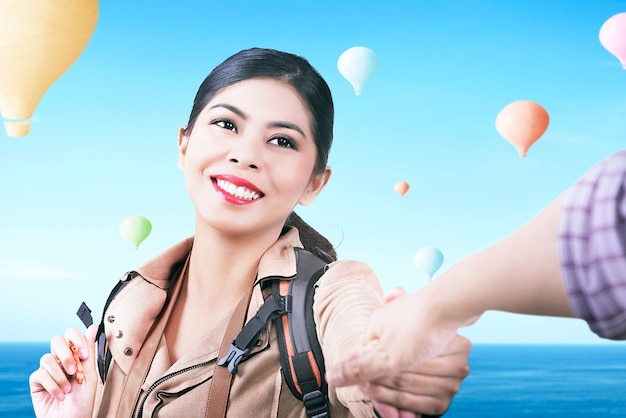Asian woman with backpack looking at colorful air balloon flying with blue sky background