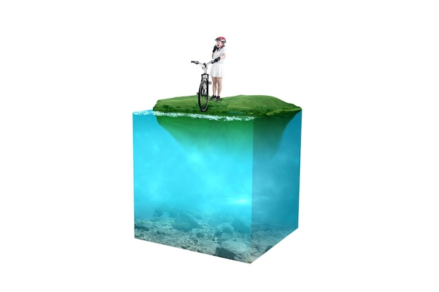 Asian woman with a bicycle helmet standing beside her bicycle on the field with an underwater view of blue water on the lake. environment concept