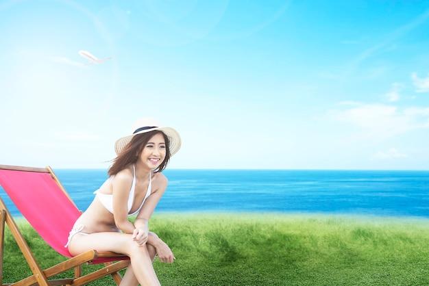 바다가 보이는 들판의 해변 의자에 앉아 비키니와 모자를 쓴 아시아 여성