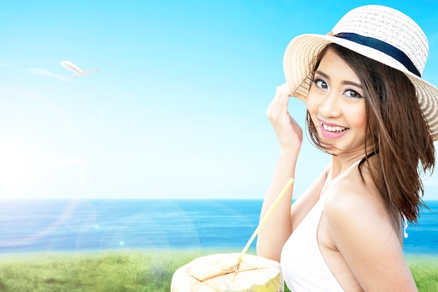 Asian woman with bikini and hat holding a coconut fruit on the field with ocean view