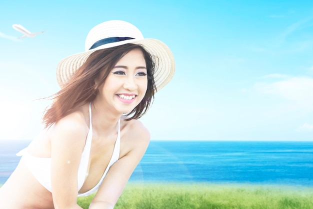 Asian woman with bikini and hat relaxing on the field with ocean view