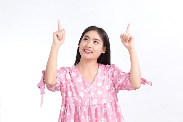 黒の長い髪のアジアの女性は、白い背景に何かを提示するために手のポイントを示しています