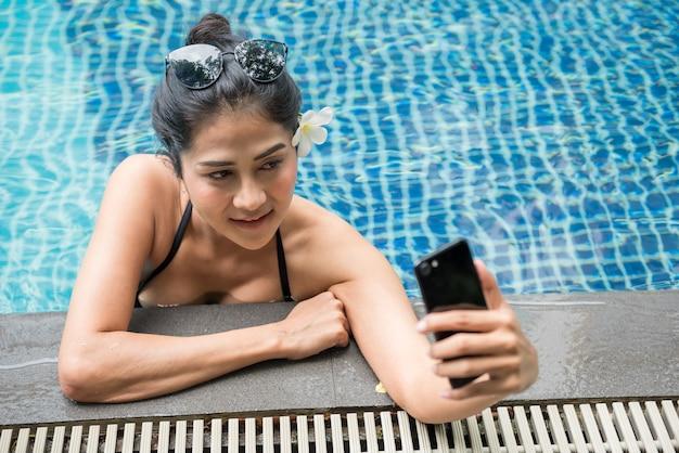 プールでスマートフォンで自分撮り黒水着のアジア人女性。
