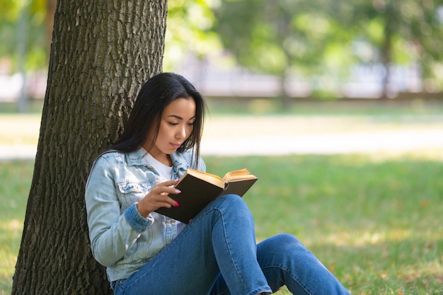 Asian woman with a book under the tree in the park the digital detox concept