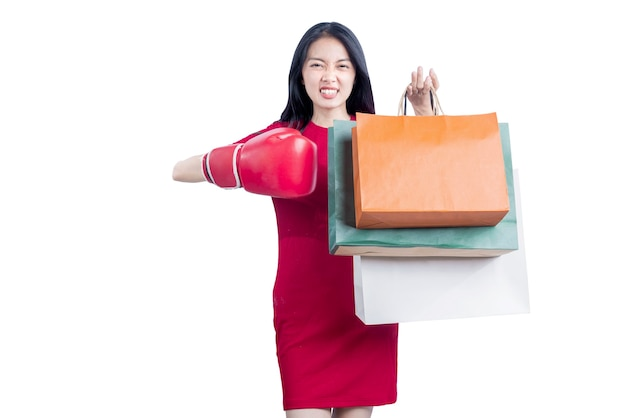 白い背景で隔離の買い物袋を運ぶボクシンググローブを持つアジアの女性