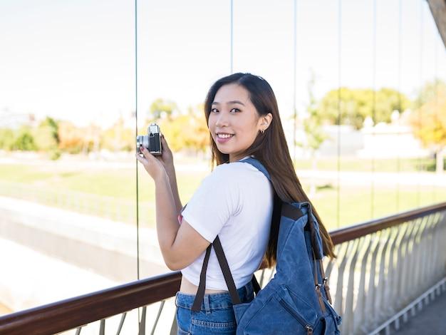 市内のカメラとバックパックを持つアジアの女性