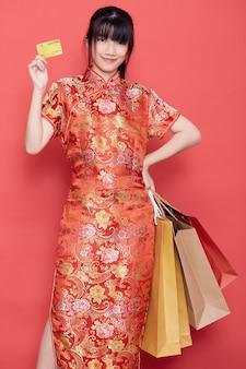 Азиатская женщина в китайском платье держит кредитную карту и сумки для покупок