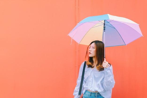 赤い壁の背景にカラフルな傘を持つアジアの女性。