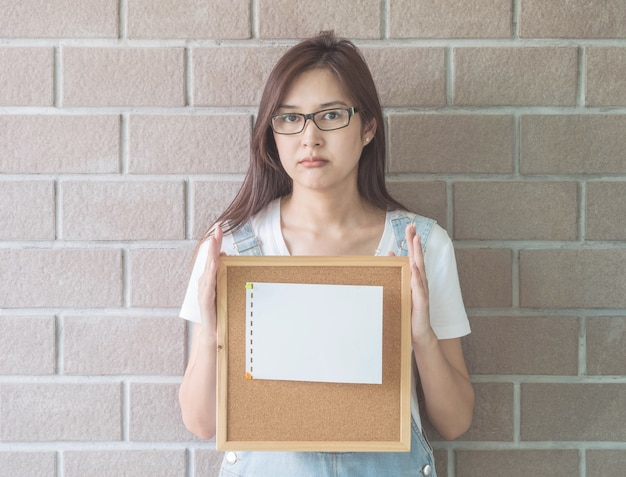 Asian woman with cork board in hand with frown face