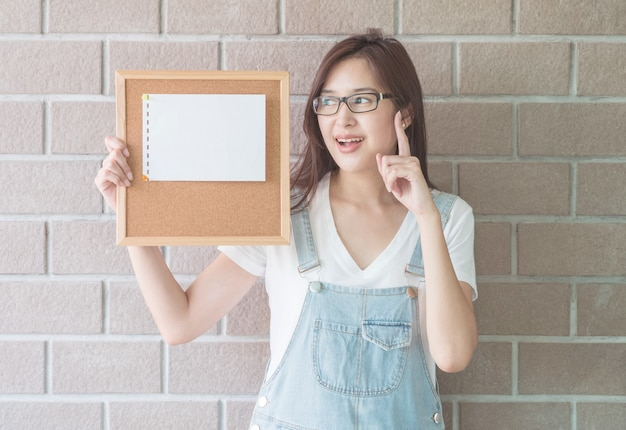 Asian woman with cork board in hand with have an idea face