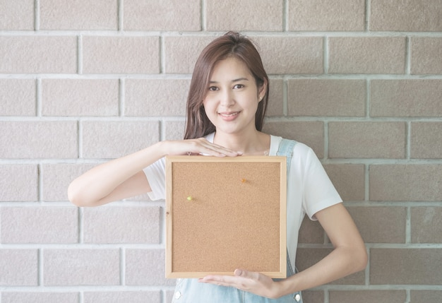 Asian woman with cork board in hand with smiling face