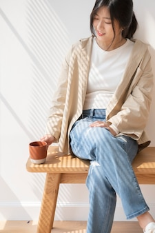 Asian woman with a cup of coffee in her hand