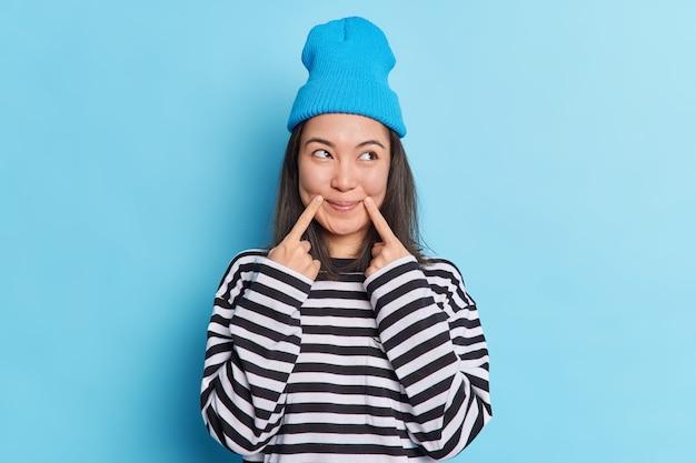 黒髪のアジア人女性が唇の角の近くで指を保ち、表情を脇に置いて満足しています