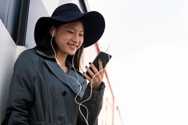 Азиатская женщина с наушниками делает видеозвонок