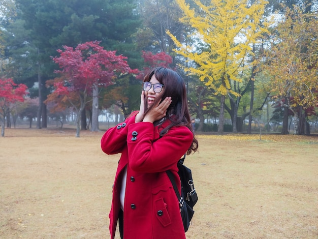 Asian woman with eyeglasses in red coat feel very happy at colorful autumn park in foggy day