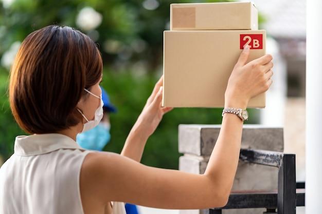 Азиатская женщина с клиентом в маске принимает пакеты с покупками у бесконтактного курьера