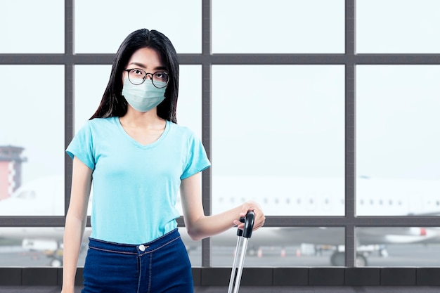 Asian woman with a face mask and glasses standing with a suitcase at the airport terminal. traveling in the new normal