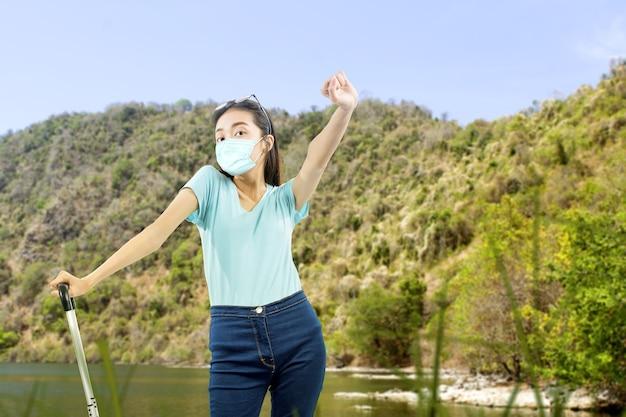 Азиатская женщина с лицевой маской стоя с чемоданом на поле. путешествие в новой норме