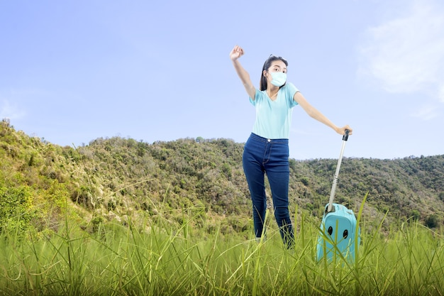 Asian woman with face mask standing with a suitcase on the field. traveling in the new normal