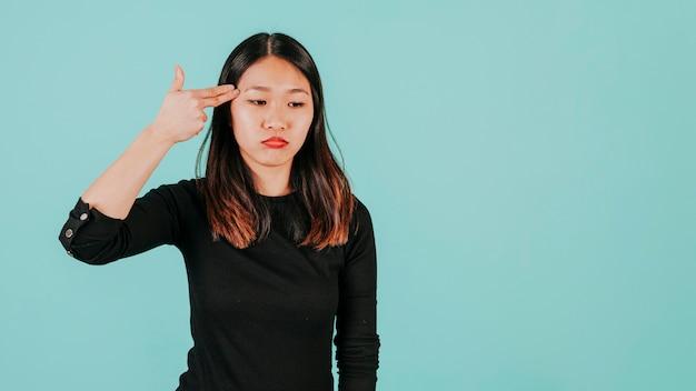 頭の近くに指の銃を持つアジアの女性