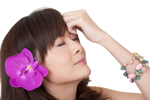 Азиатская женщина с цветком на голове, портрет крупным планом на белом.