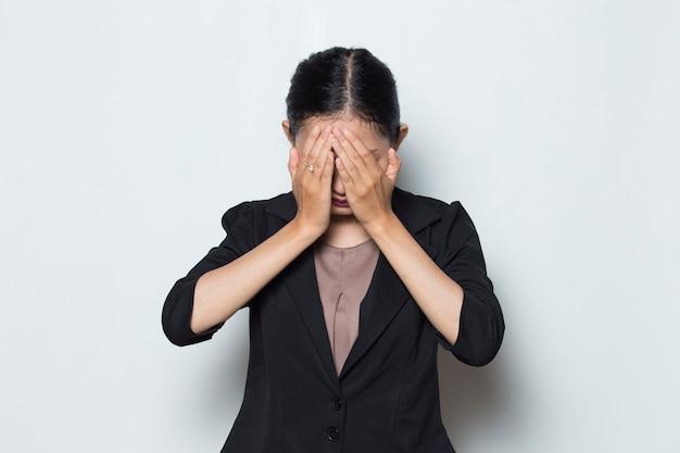 공식적인 복장을 한 아시아 여성이 흰색 배경에 손으로 얼굴을 가립니다.