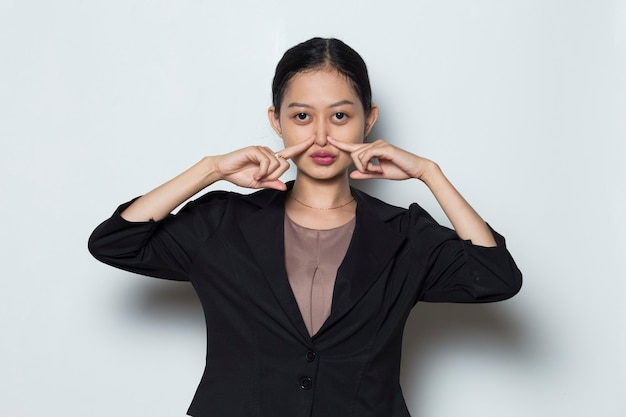 Asian woman with formal outfit holding her nose because of a bad smell