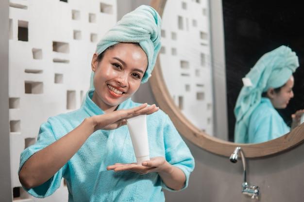 フェイシャルトリートメントクリームのモックアップを保持している新鮮な肌を持つアジアの女性